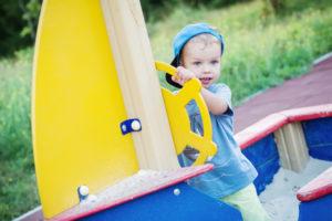 Junge hat Spaß im Sandkastenschiff